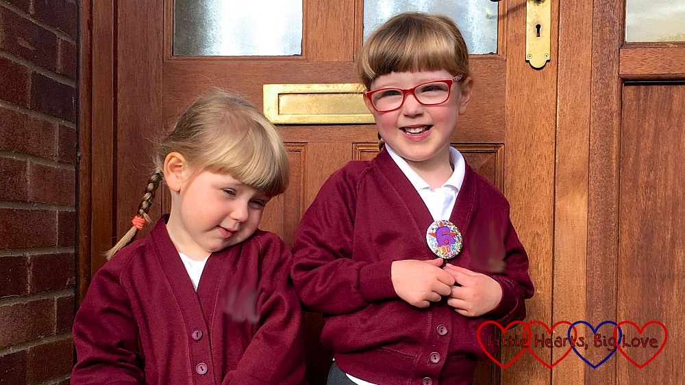 Jessica and Sophie outside the door - Jessica in her school uniform and Sophie in her preschool jumper