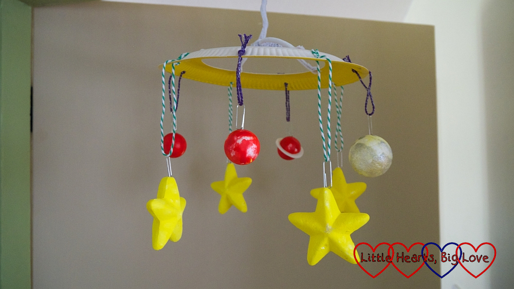 """A space-themed mobile with polystyrene stars and """"planets"""""""