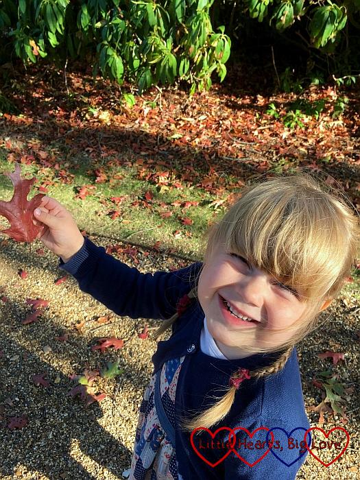 Sophie holding up a brown leaf
