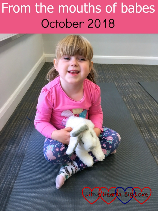 "Sophie sitting cross-legged on a yoga mat holding the class bunny - ""From the mouths of babes - October 2018"""