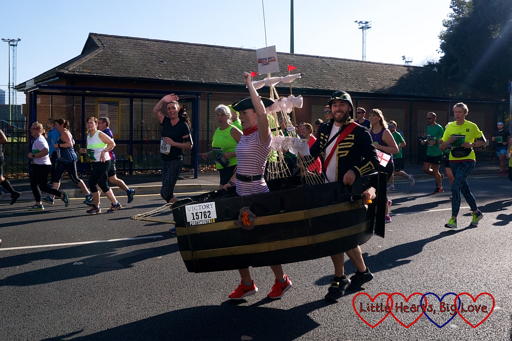 Two runners running whilst wearing a model of HMS Victory