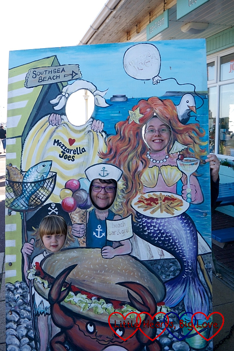 Me, Maxine and Sophie looking through a seaside peephole board with fish and mermaids