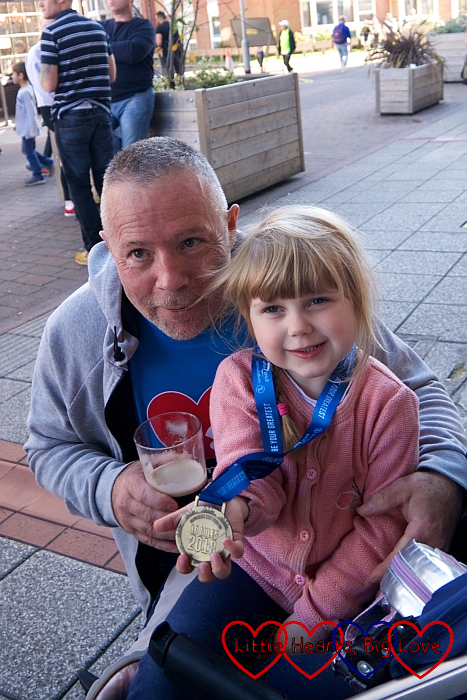Uncle Adrian and Sophie holding Uncle Adrian's medal