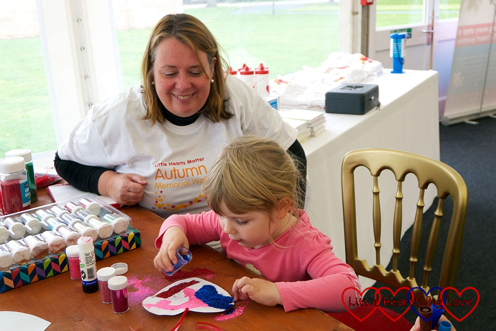 Sophie decorating a paper heart with Suzie from Little Hearts Matter