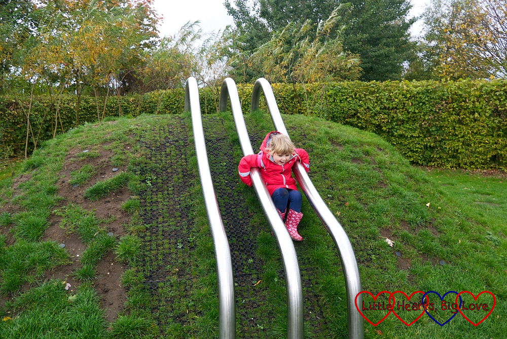 Sophie sliding down the bannister slide in the sensory garden