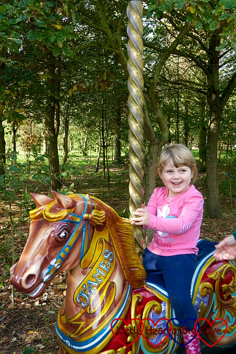 A smiley Sophie sitting on the carousel horse at the Showman's Guild memorial