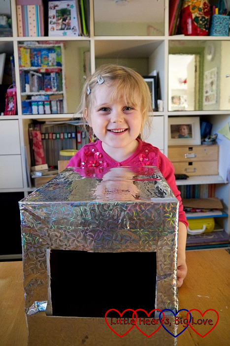 Sophie showing our box covered with shiny silver paper
