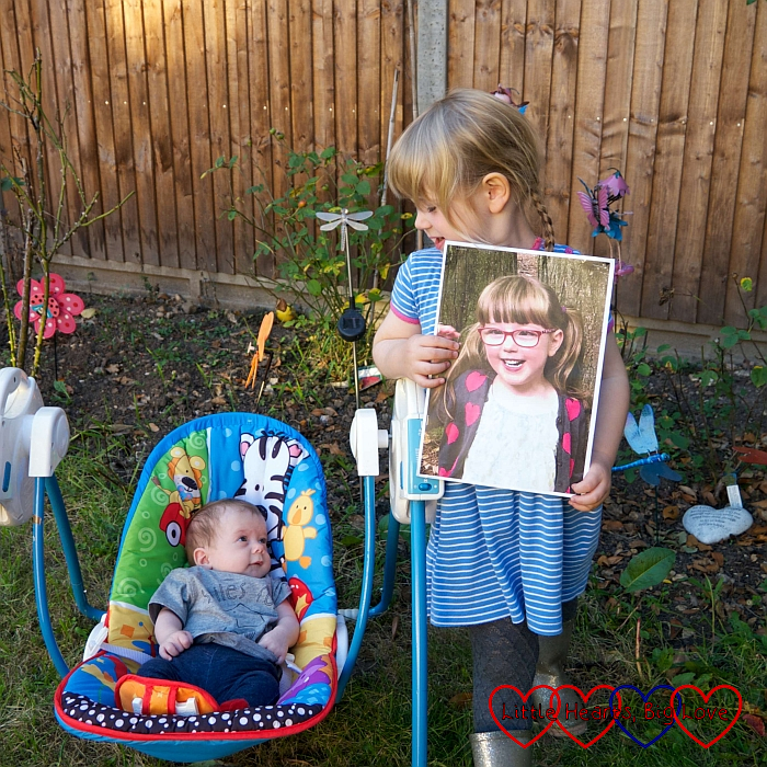 Sophie and Thomas in the garden with a picture of Jessica