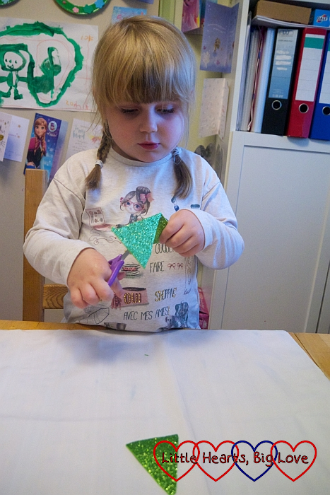 Sophie cutting triangles from sparkly green craft foam