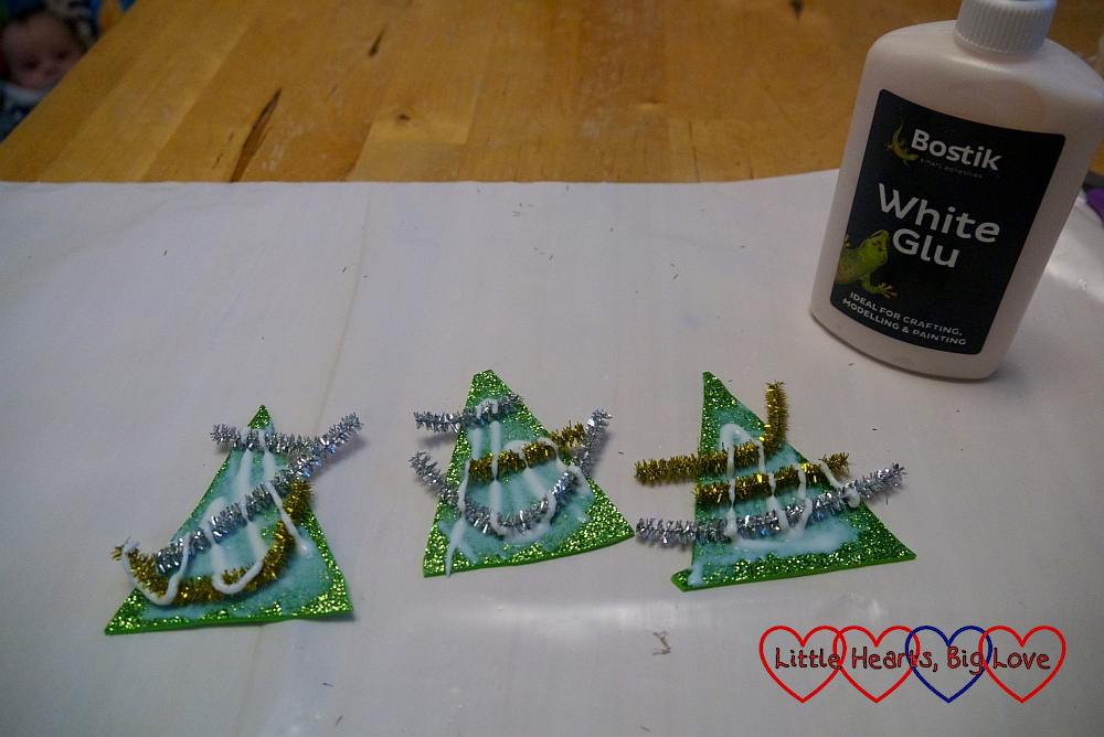 Pieces of tinsel glued on to sparkly green craft foam triangles