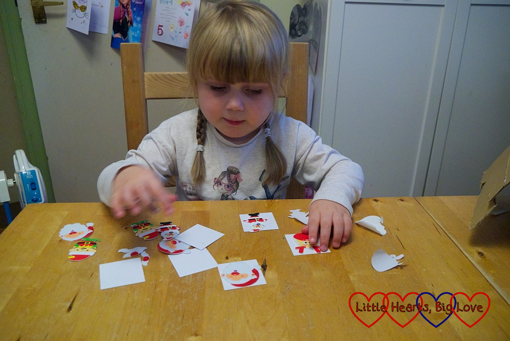 Sophie sticking festive stickers to squares of white card