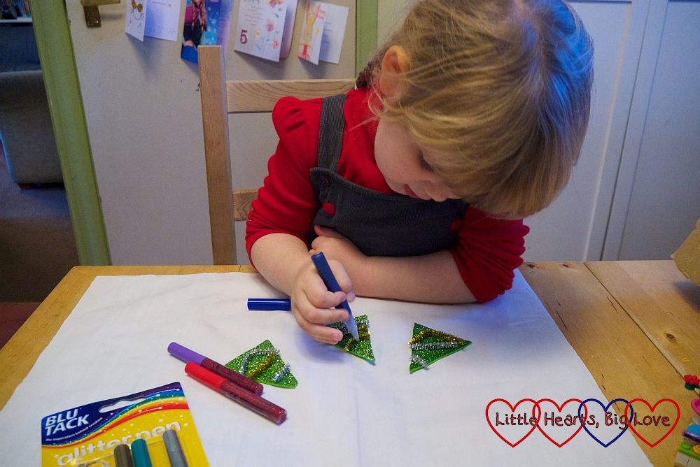 Sophie using a glitter pen to add coloured dots to the sparkly green craft foam triangle