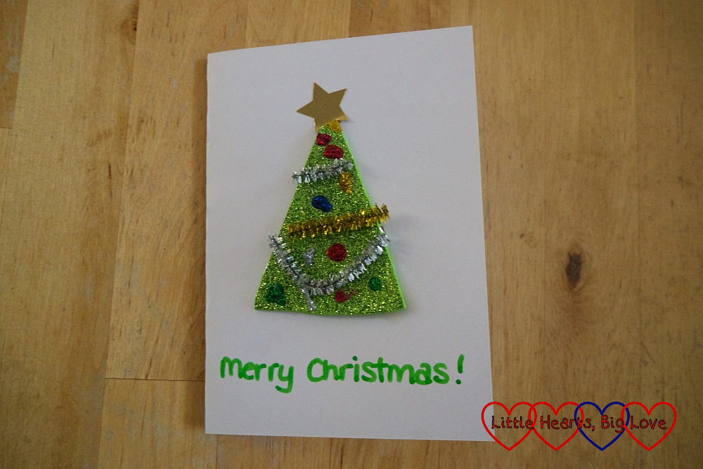 "A card with a sparkly green craft foam Christmas tree on front and ""Merry Christmas"" written below"