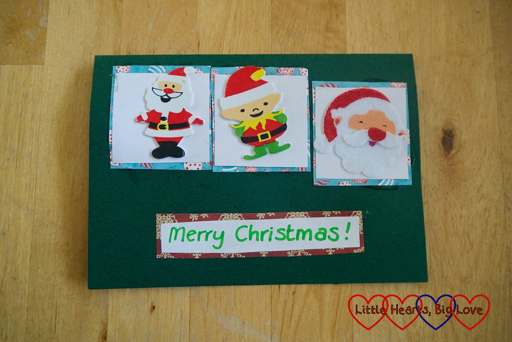 "A handmade Christmas card with three squares each with a festive sticker and ""Merry Christmas"" below the squares"