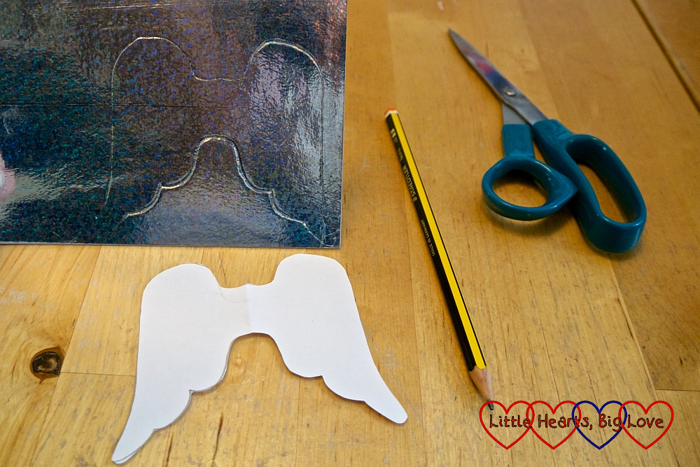 A paper angel wings template and angel wings marked out on a piece of silver card with a pencil and scissor next to them on the table