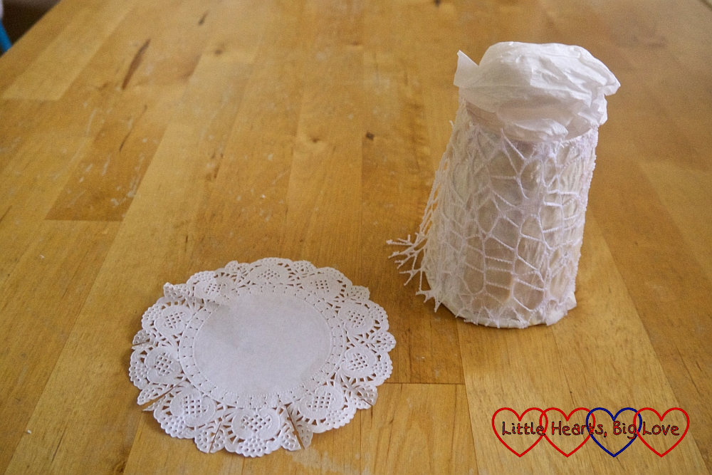 The paper cup with scrunched up white crepe paper on top and a paper doily next to it