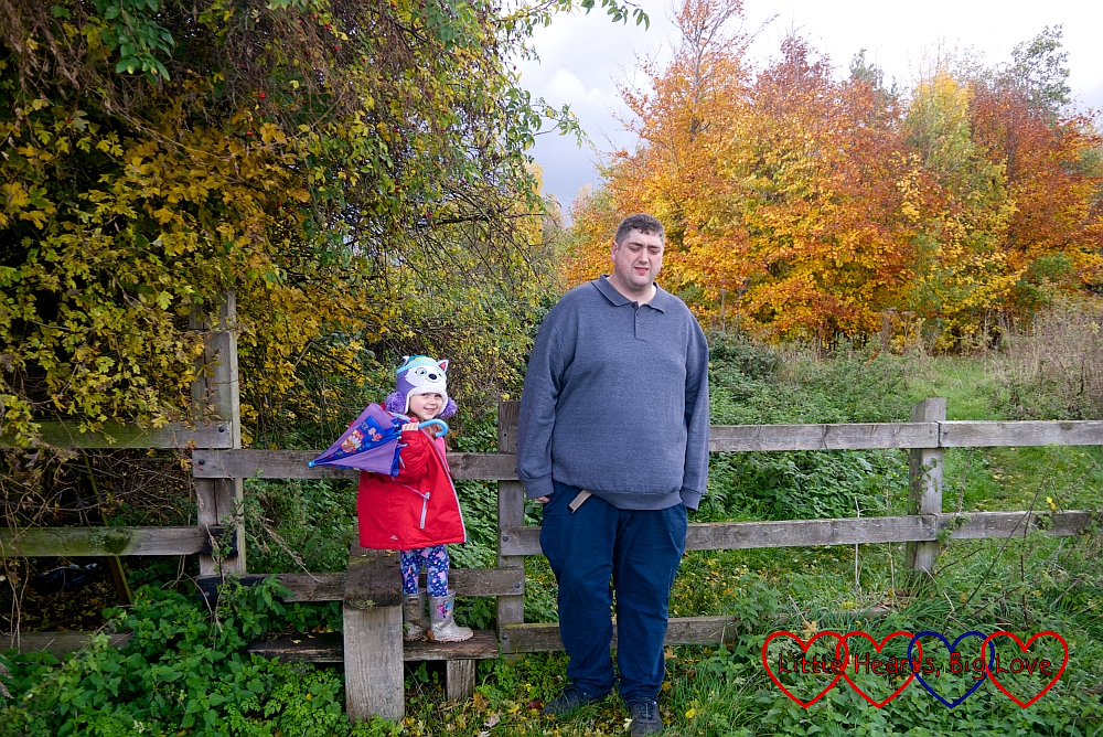 Sophie standing on a stile next to hubby against a backdrop of autumn trees