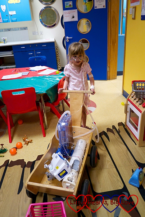 Jessica pushing her trolley with her drains in the playroom on Ocean Ward