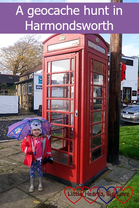 "Sophie standing outside a red telephone box with her umbrella - ""A geocache hunt in Harmondsworth"""