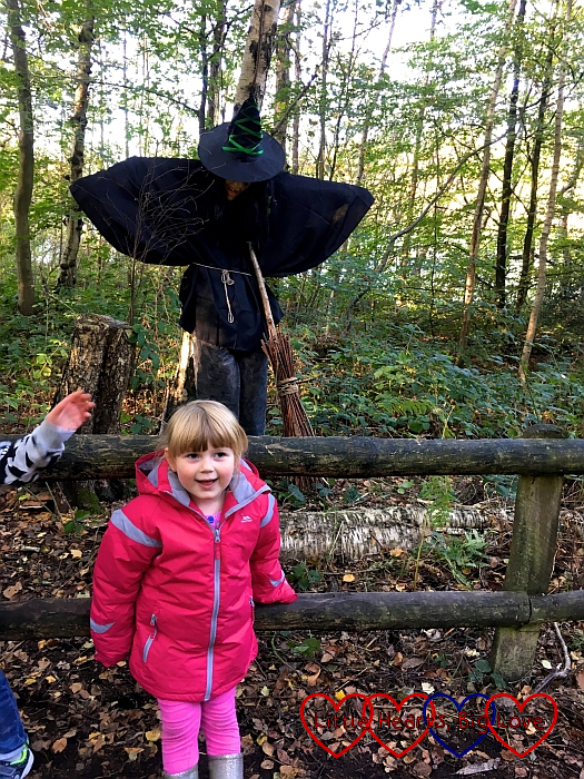 Sophie standing in front of the witch scarecrow