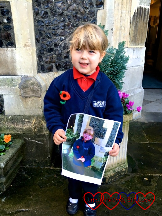 Sophie standing outside the church in her Girls' Brigade uniform holding the picture of Jessica taken at last year's Remembrance Sunday parade