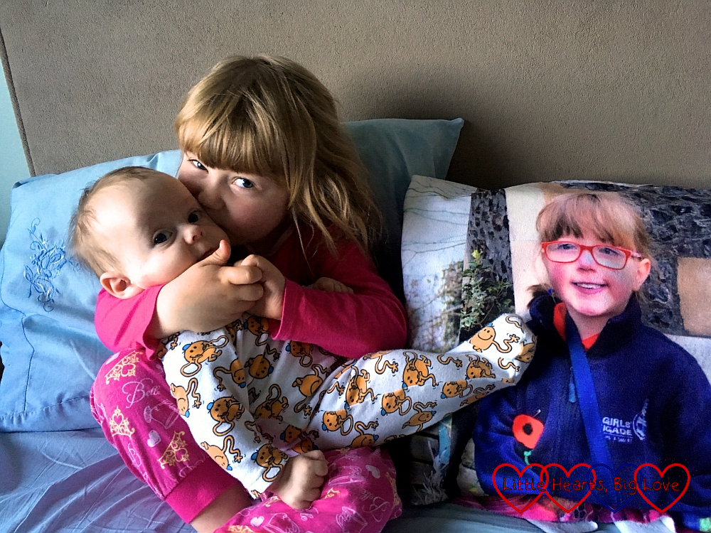 Sophie cuddling Thomas and giving him a kiss with Jessica looking on from a photo on her photo blanket
