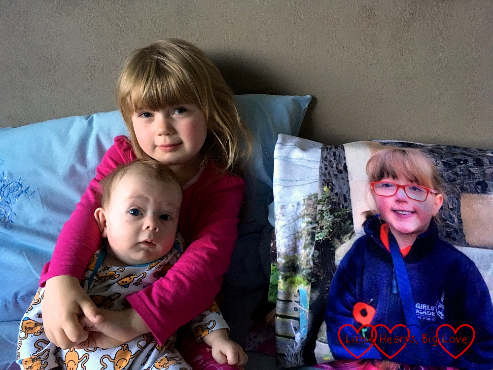 Sophie cuddling Thomas with Jessica looking on from a photo on her photo blanket