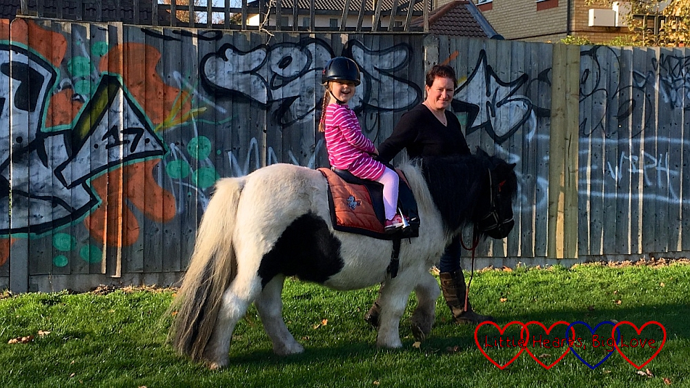 A very smiley Sophie riding a white and brown Shetland pony