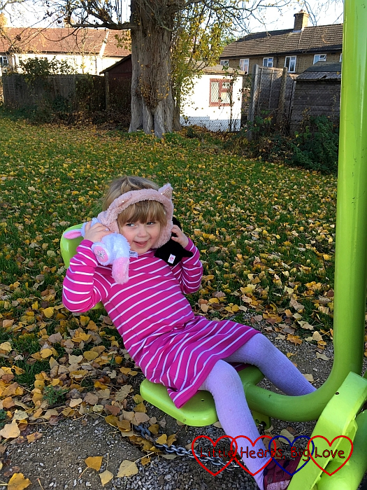 Sophie sitting on the outdoor gym equipment with her cat ear muffs on