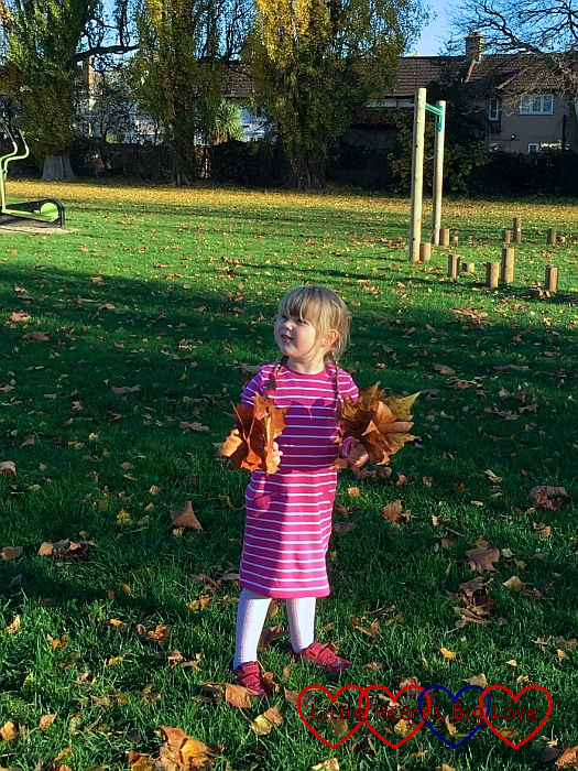 Sophie holding a handful of autumn leaves in each hand