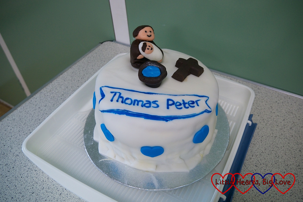 Thomas's christening cake with icing figures of a vicar holding a baby in front of a font and an icing cross