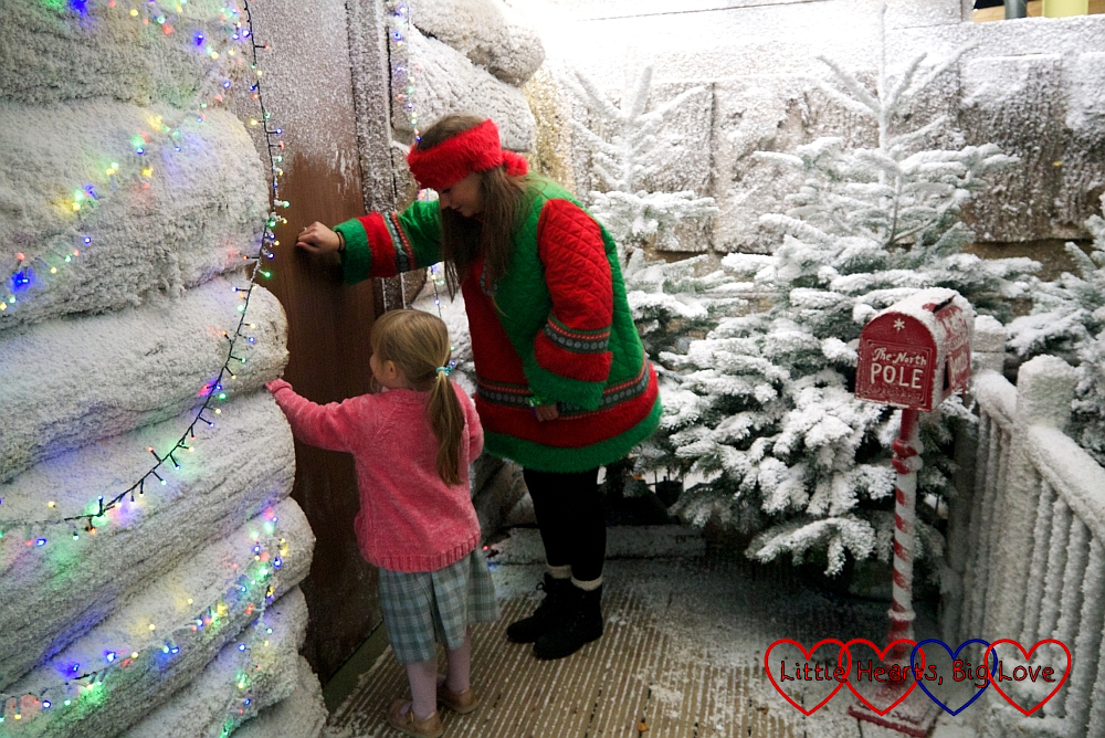 Sophie and Tiny the Elf knocking at the door of Santa's cabin