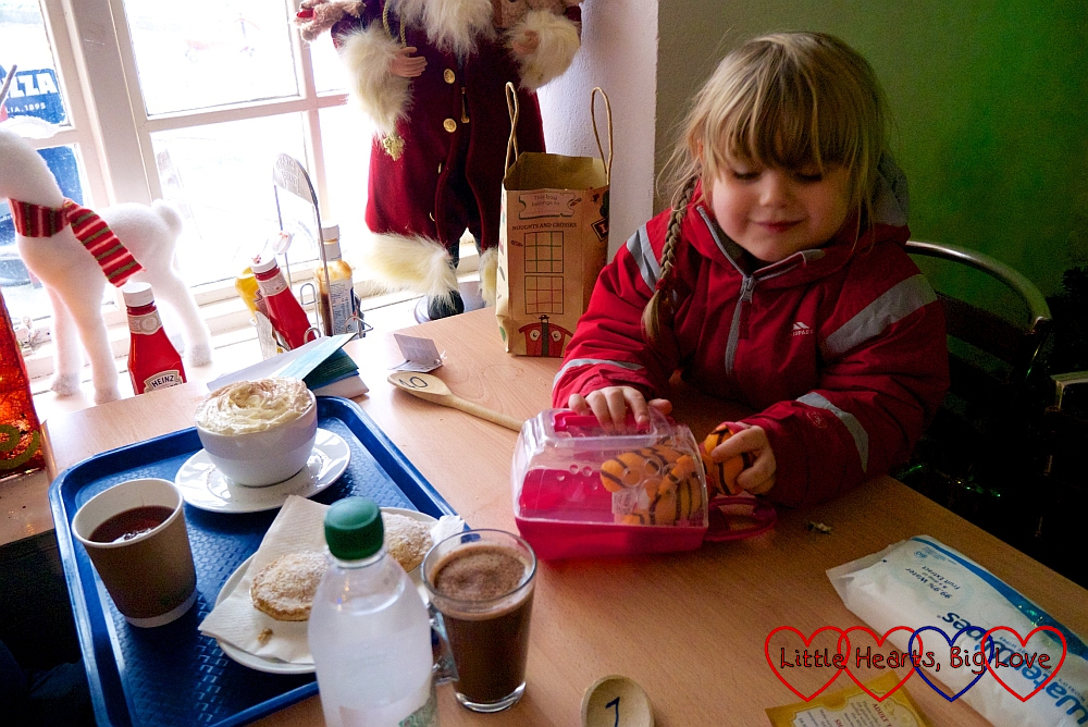 Sophie playing with her soft toy cat while we enjoy a mince pie and hot drink