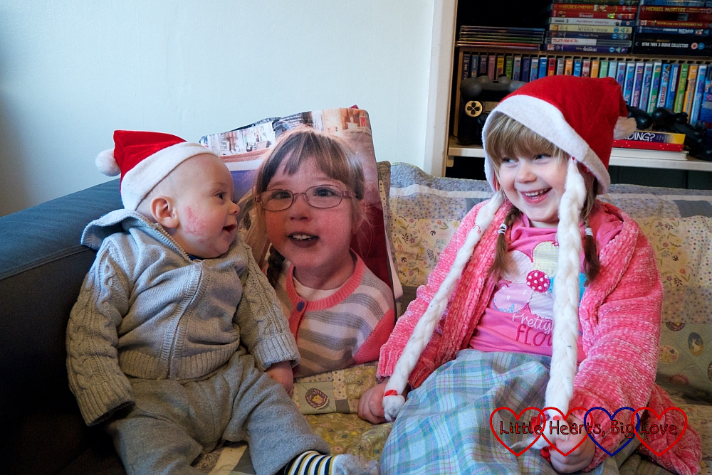 Sophie and Thomas looking at each other and smiling, wearing Santa hats, with Jessica's picture between them