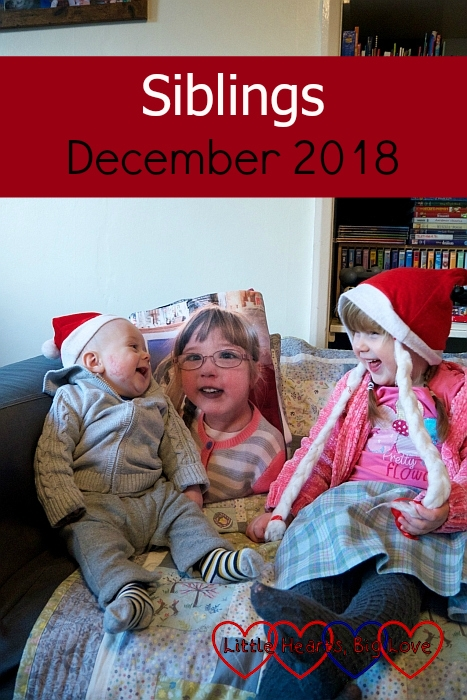 "Sophie and Thomas looking at each other and smiling, wearing Santa hats, with Jessica's picture between them - ""Siblings - December 2018"""