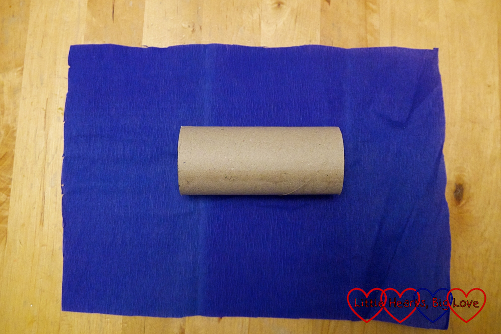 A tpilet roll in the middle of a piece of blue crepe paper
