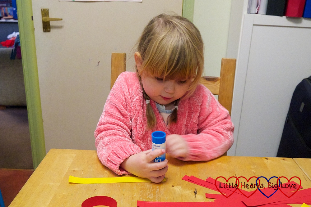 Sophie gluing one end of a coloured paper strip