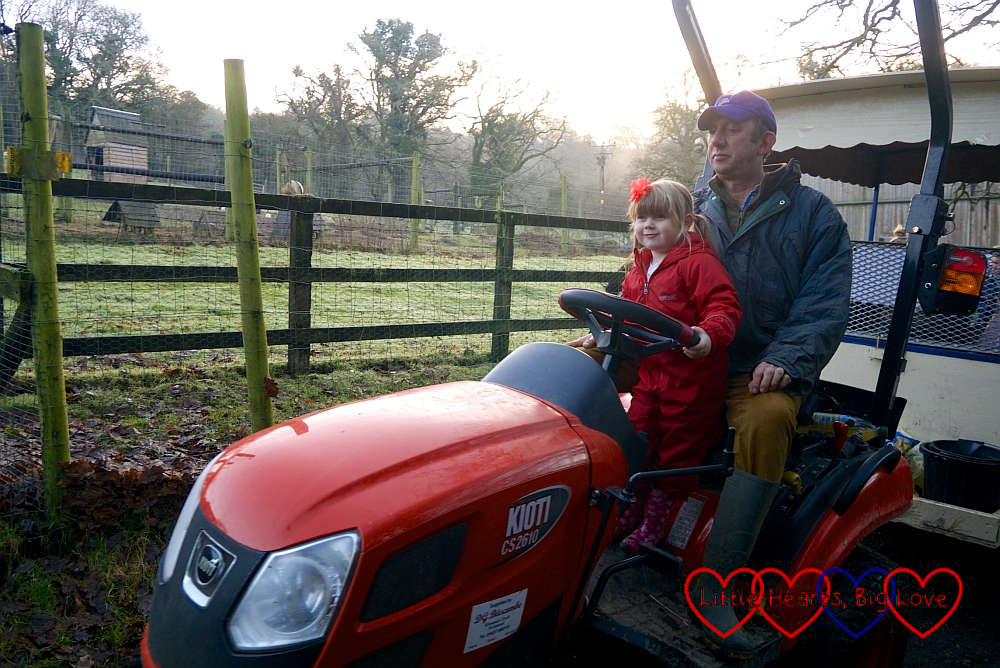 Sophie driving the tractor with Farmer Nick