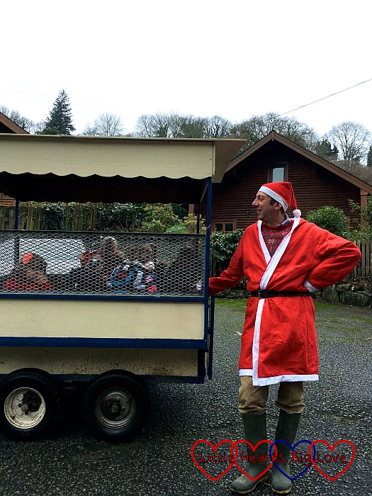 Farmer Christmas standing next to the children's trailer