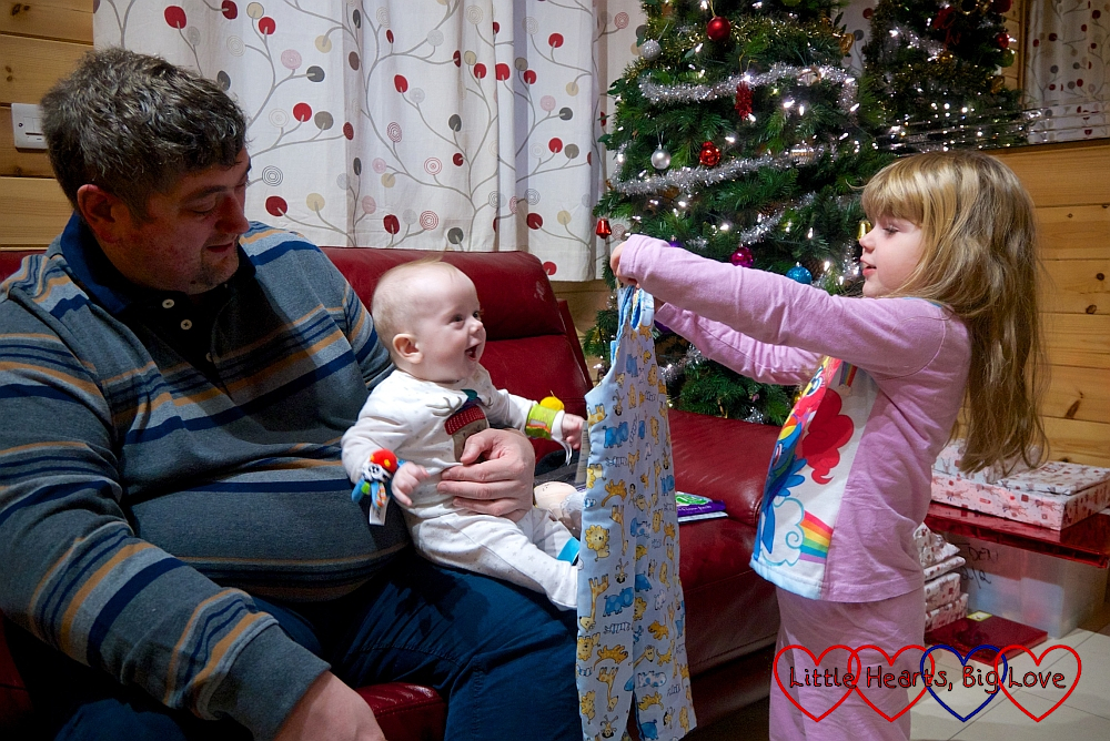 Hubby holding a smiley Thomas on Christmas Day while Sophie holds up a pair of dungarees (one of Thomas's christmas presents)