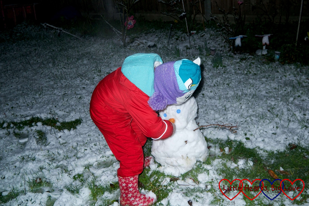 Sophie making a snowman with blue button eyes and a carrot nose
