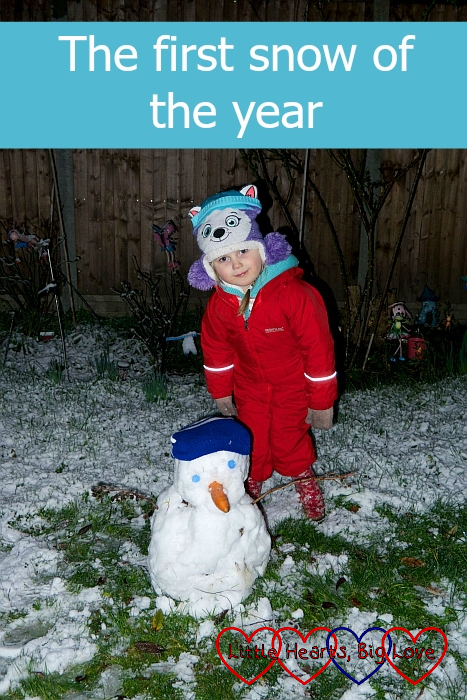 "Sophie in her red puddlesuit next to a snowman - ""The first snow of the year"""