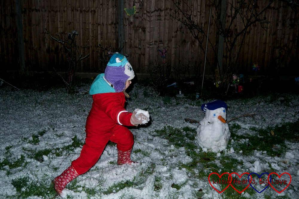 Sophie throwing snowballs at her snowman