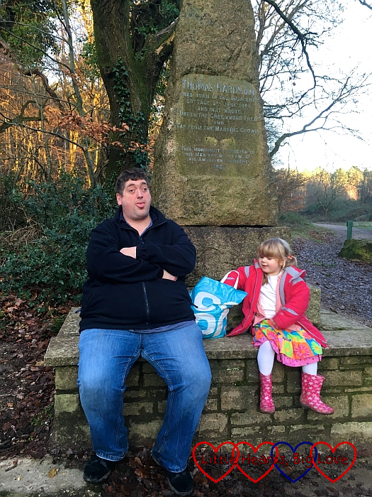 Hubby and Sophie sitting on the memorial next to Hardy's Cottage