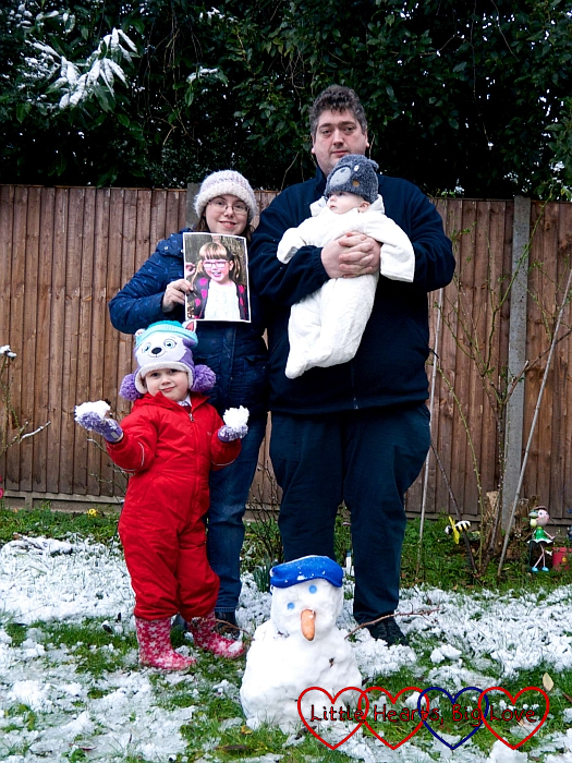 Sophie, hubby, Thomas and me holding a picture of Jessica next to the snowman Sophie built