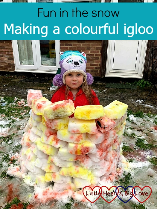 "Sophie behind the wall of coloured snow bricks - ""Fun in the snow: Making a colourful igloo"""