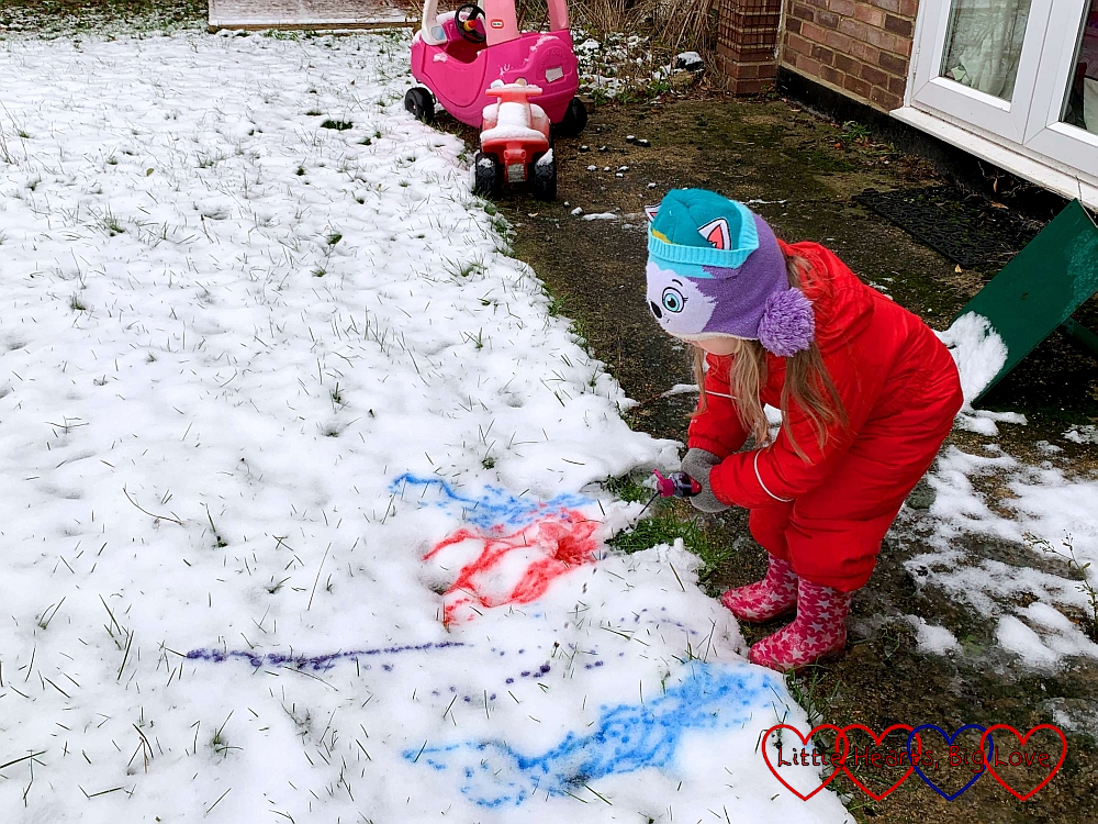 Sophie squirting coloured water on the snow