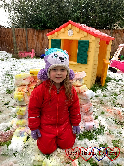Sophie standing in front of her colourful igloo