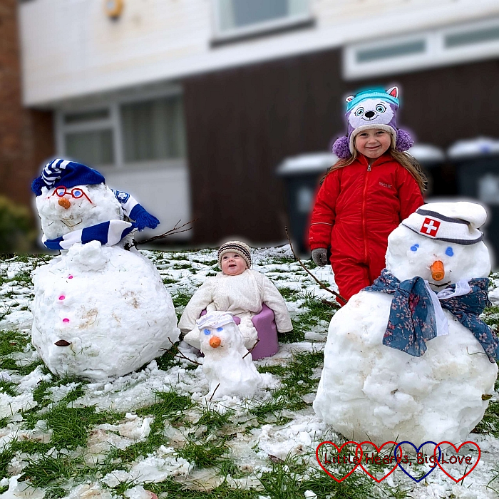 Sophie and Thomas with a family of three snowmen - one large, one medium-sized and one small one