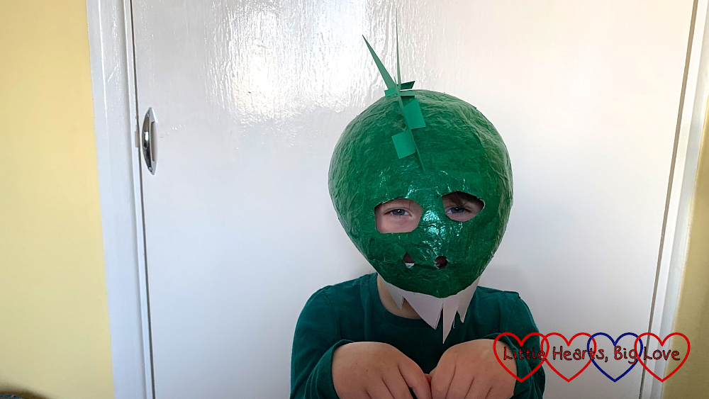 Sophie wearing a dinosaur head made from papier-mache